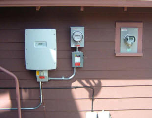 From left to right: SMA 7000 watt grid tied synchronous inverter with integrated DC disconnect, system production meter above the AC disconnect (middle), and the utility revenue meter (pre-existing) which has been retrofitted by the utility to be a net meter capable of metering both incoming and outgoing electricity.  Not pictured is the home's electrical panel (inside) behind the utility net meter where the PV system interconnects with the grid via a two pole breaker.