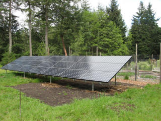 """This ground mounted array on Bainbridge Island uses 2"""" heavy duty galvanized pipe. This type of structure works well for large ground mounted systems and is adaptable to uneven terrain."""
