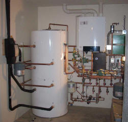 A nearly complete integration of a solar thermal system.  A 120 gallon storage tank is on the left.  Note the plumbing entering the tank.  This tank contains three heat exchange loops, one for the solar thermal (bottom) one for the back up heat source (middle) and one to the radiant floors (top).  An on-demand propane boiler provides back up heat.  Other equipment includes the floor radiant heat controls.
